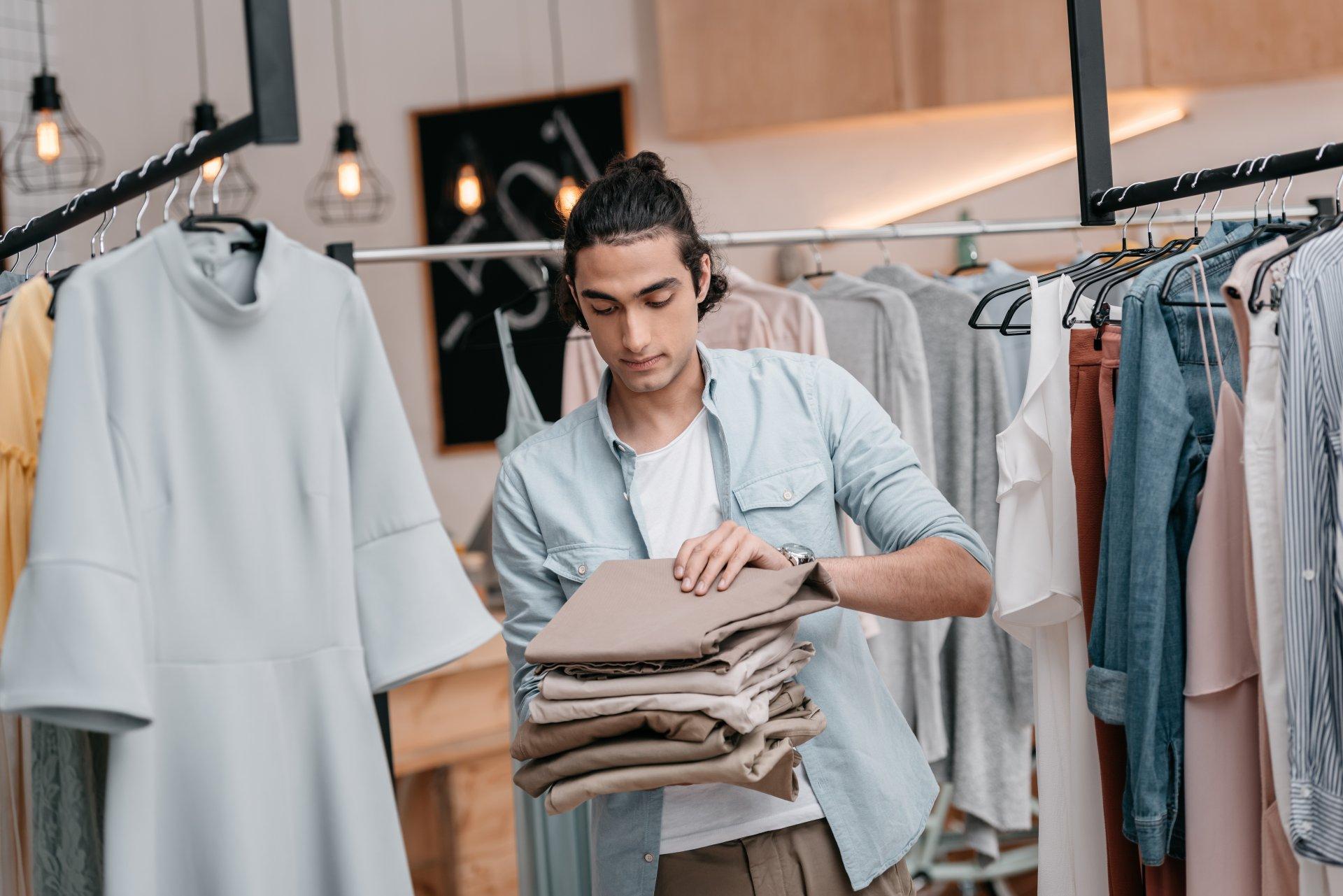 Jonge man die broeken aan het vouwen is in een winkel omringd door andere kledingstukken. Afbeelding is puur decoratief.