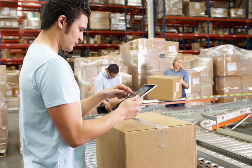 Jonge man in een warehouse aan het werk. Afbeelding is puur decoratief.