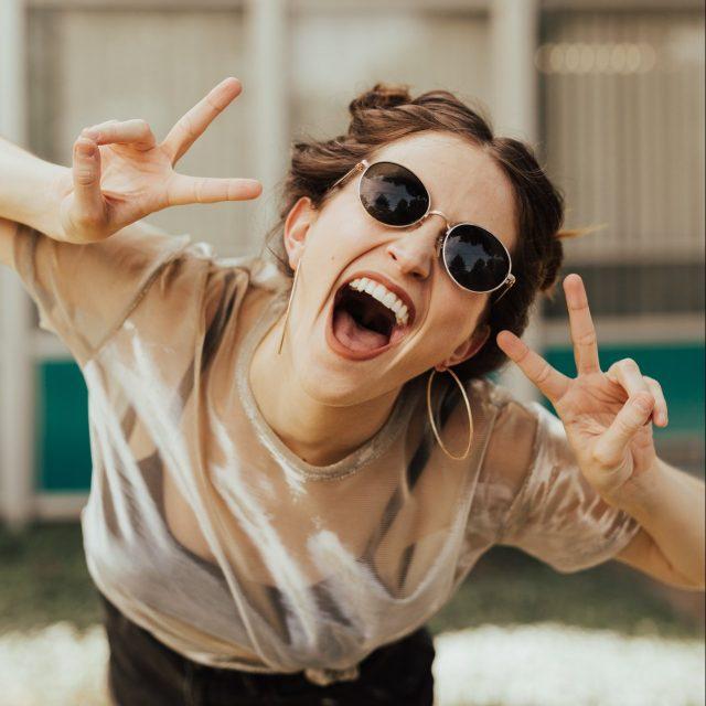 Vrolijke dame die lachend naar de camera kijkt met haar handen als peace teken in te lucht. Afbeelding is puur decoratief.