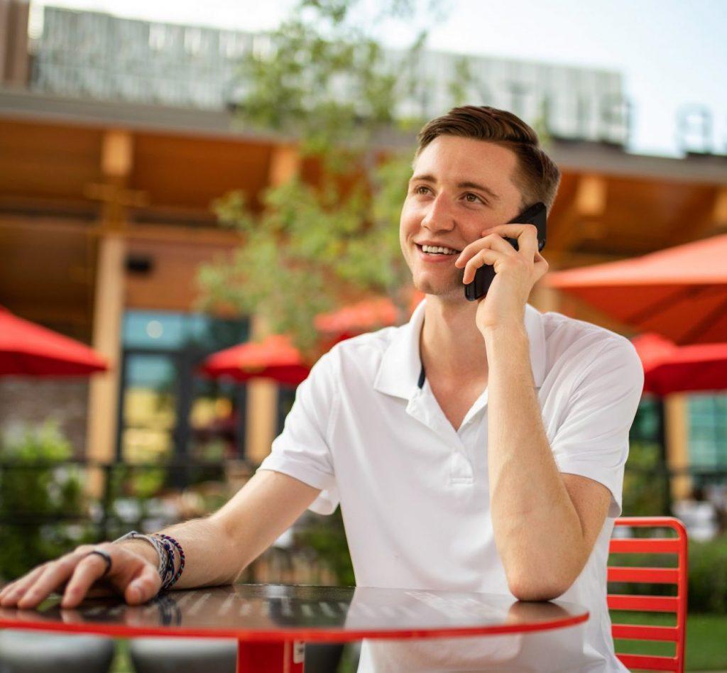 Jonge man die op het terras aan het bellen is. Afbeelding is puur decoratief.