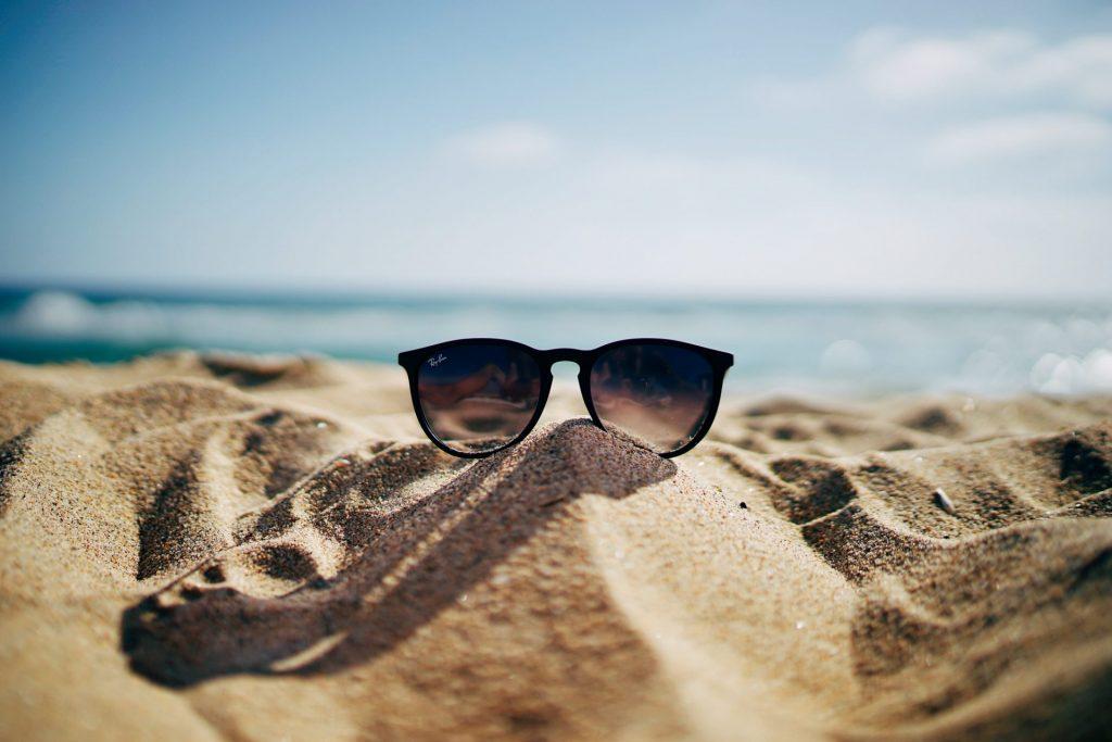 Uitgelichte afbeelding voor de blog voorbereid de zomer in. Een zonnebril die op het strand ligt. Deze afbeelding is puur decoratief.