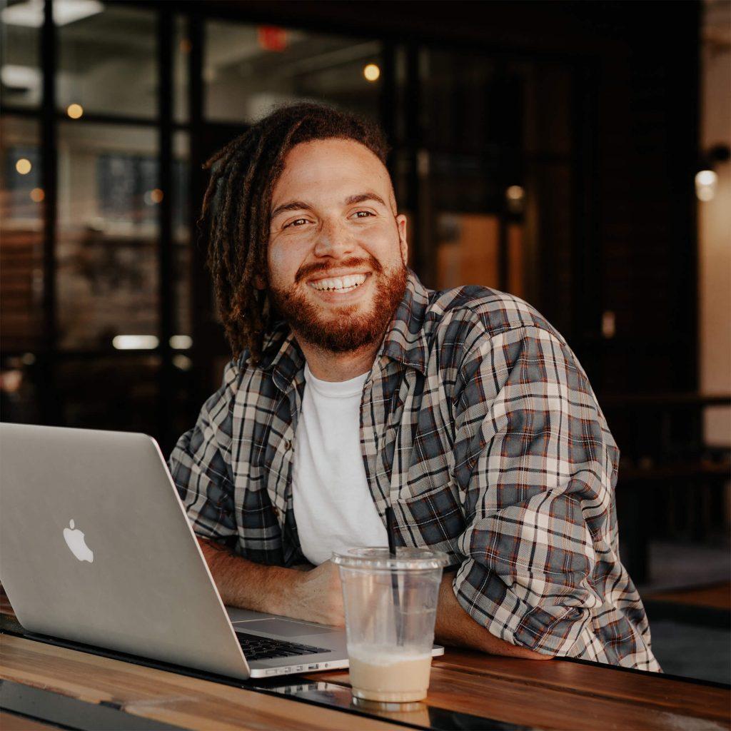 Een lachende man die achter zijn laptop zit. Deze foto is puur decoratief.