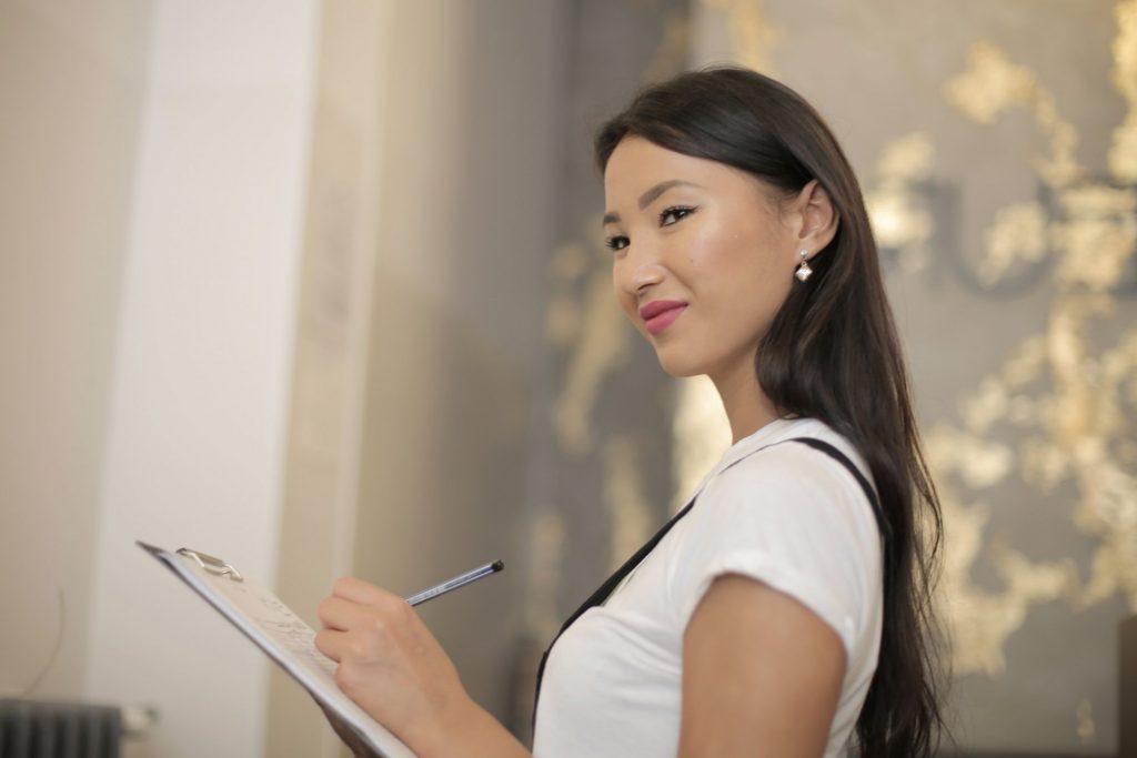 Jonge dame met een klapbord in haar handen. Afbeelding is puur decoratief.