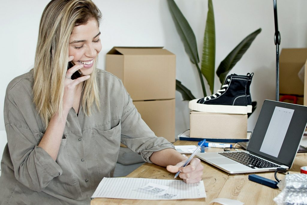 Vrouw aan de telefoon terwijl ze aantekeningen maakt. Afbeelding is puur decoratief.