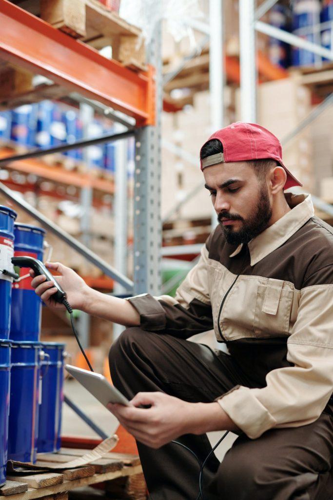 Jonge man aan het werk in een logistiek warehouse waar hij producten aan het scannen/checken is. Afbeelding is puur decoratief.