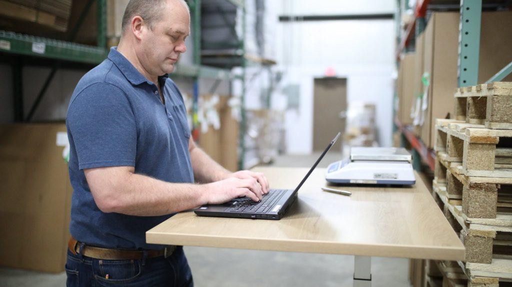 Een meneer die achter zijn laptop aan een staand-bureau staat. Afbeelding is puur decoratief.