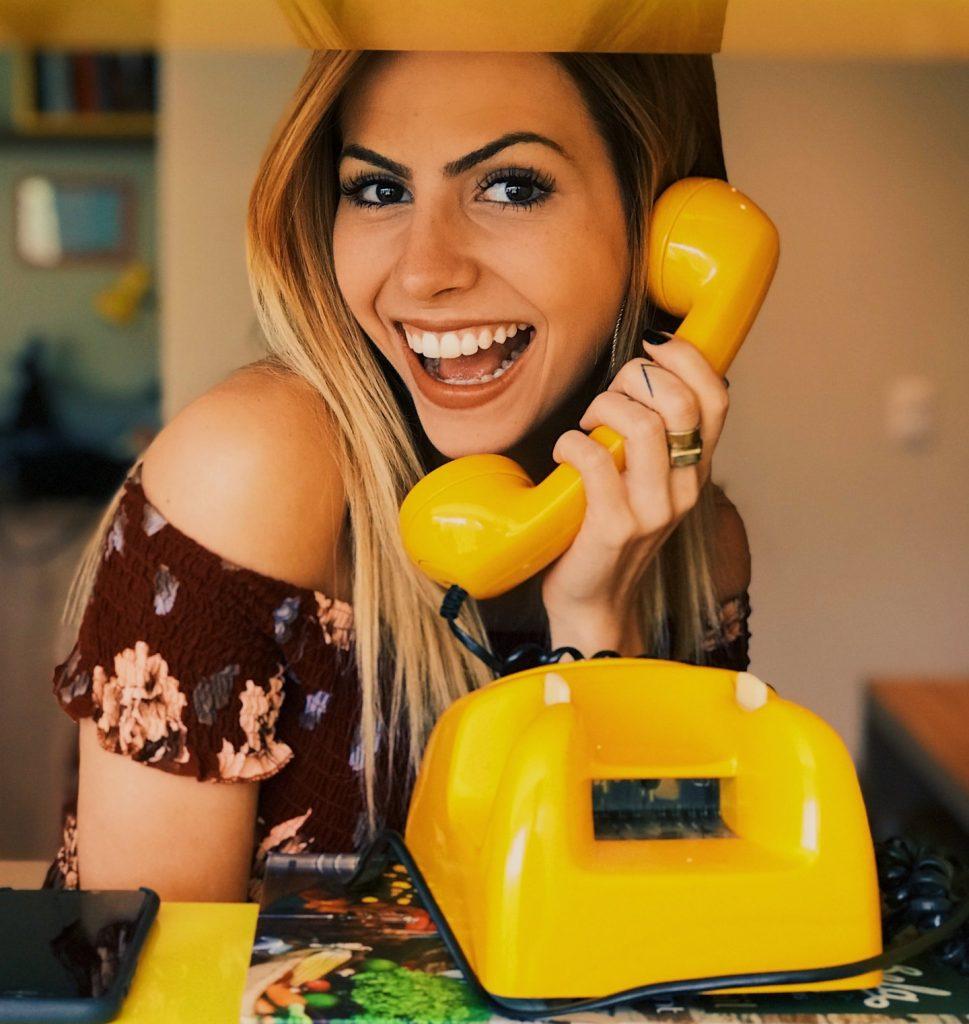 Vrolijke jonge dame met een knalgele ouderwetse telefoon in haar handen. Afbeelding is puur decoratief.