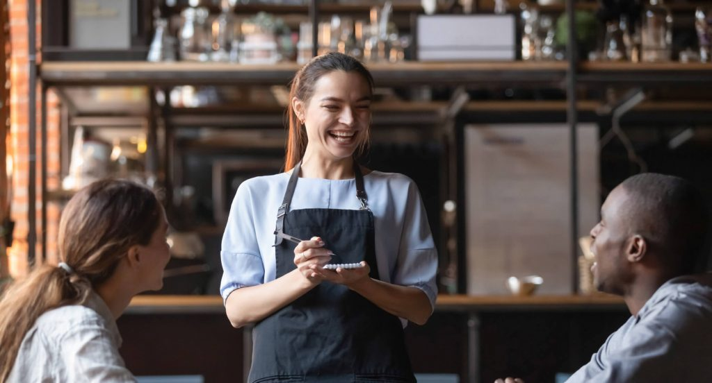 Een vrouwelijke ober die lachend de bestelling van twee klanten opneemt. De afbeelding is puur decoratief.